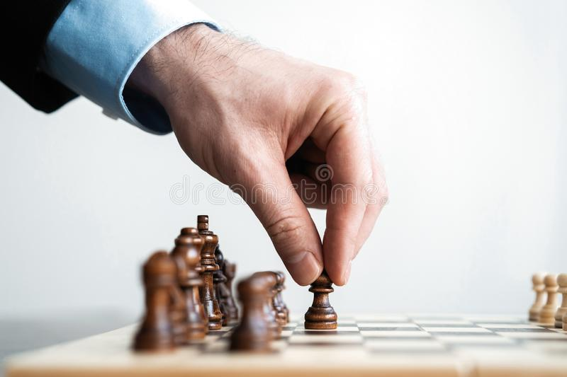 Hand of businessman moving chess figure in competition success play. strategy, management or leadership concept. royalty free stock photos