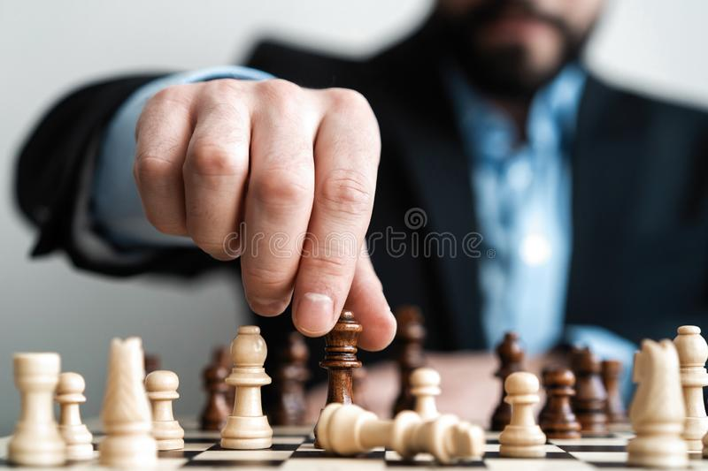 Hand of businessman moving chess figure in competition success play. strategy, management or leadership concept. stock photos