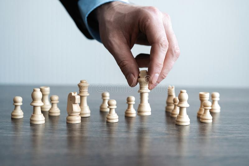 Hand of businessman moving chess figure in competition success play. strategy, management or leadership concept. royalty free stock photo
