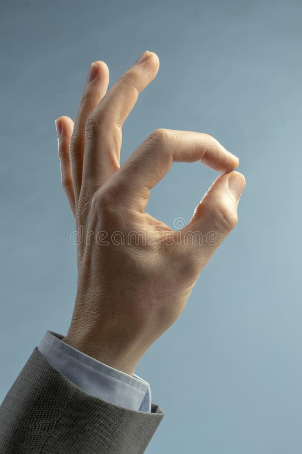 Hand of businessman in ok sign on a light blue background royalty free stock image