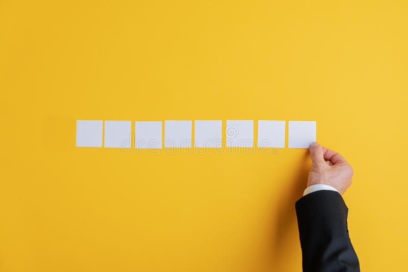 Hand of a businessman placing eight blank white post it papers in a row royalty free stock photography