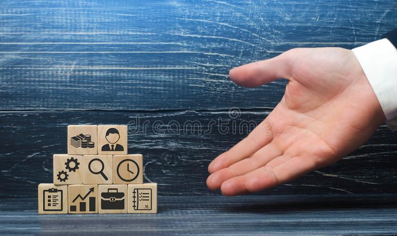 The hand of a businessman presents a recipe from business elements and attributes for a successful business. The correct construction and structure of the royalty free stock photography