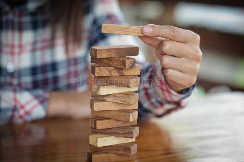 Hand of businessman pulling out or placing wood block on the tower. plan and strategy in business.  Risk management, Challenge In royalty free stock image
