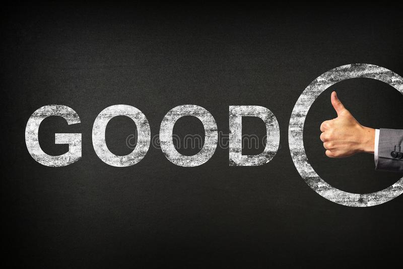 Hand of a businessman showing thumbs up for the phrase GOOD written on a blackboard royalty free stock images