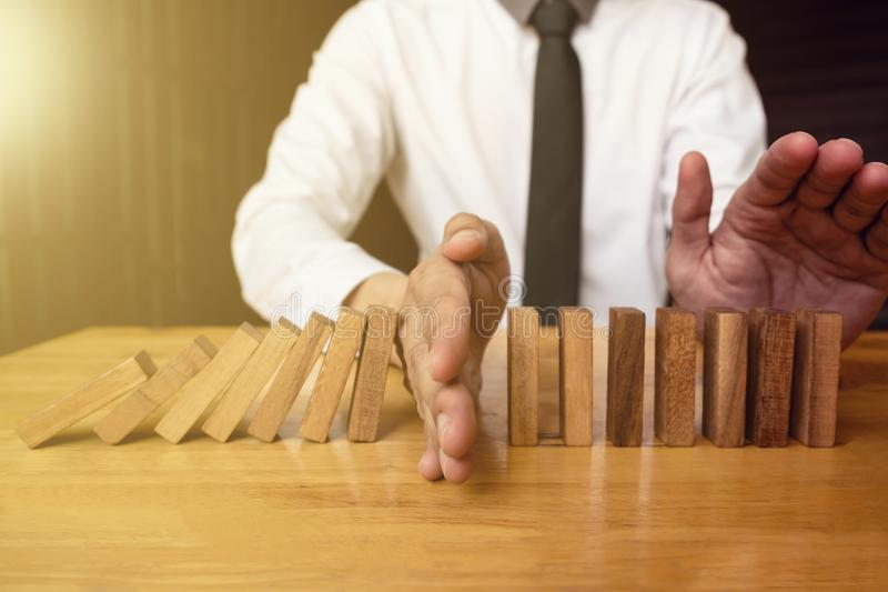 Hand of businessman is stoping falling wooden domino effect from stock photography