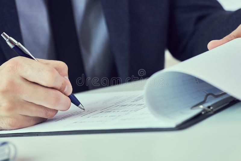 Hand of businessman in suit filling and signing with blue pen partnership agreement form clipped to pad closeup royalty free stock photo