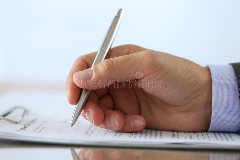 Hand of businessman in suit filling and signing partnership agre royalty free stock image