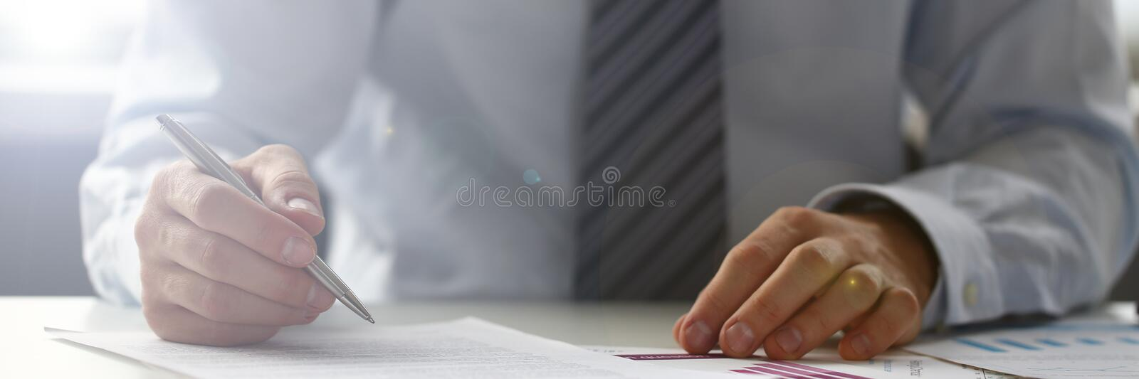 Hand of businessman in suit filling and signing with stock photos