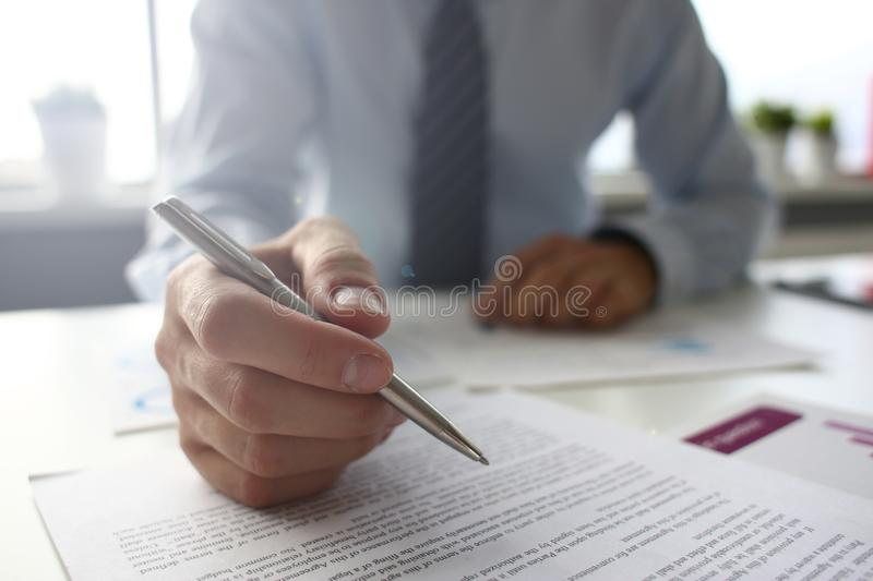 Hand of businessman in suit filling and signing with royalty free stock image
