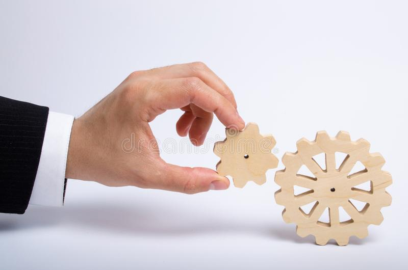 Hand of businessman in suit holds the gear to another gear wheel. The hand connects two round gears. The concept of business royalty free stock photos