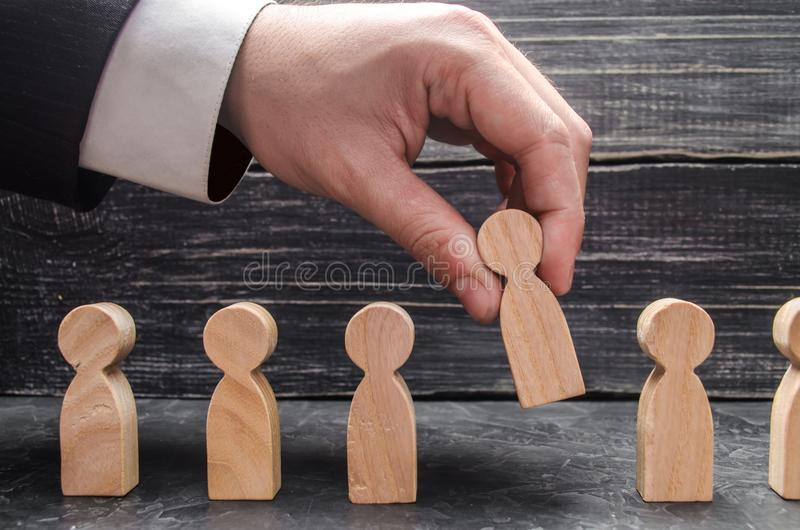 Hand of a businessman takes a wooden figure of a man. The concept of search, hiring and firing workers, promotion. Business tactics and strategy, management stock photos