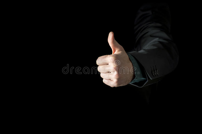 Hand of a businessman wearing black business suit showing thumb stock photos