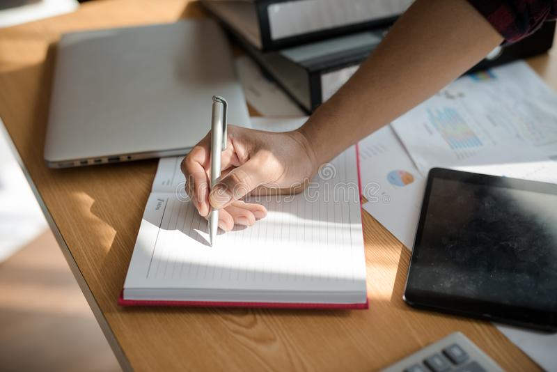 Hand of businessmen holding pen while writing notes in the book royalty free stock image