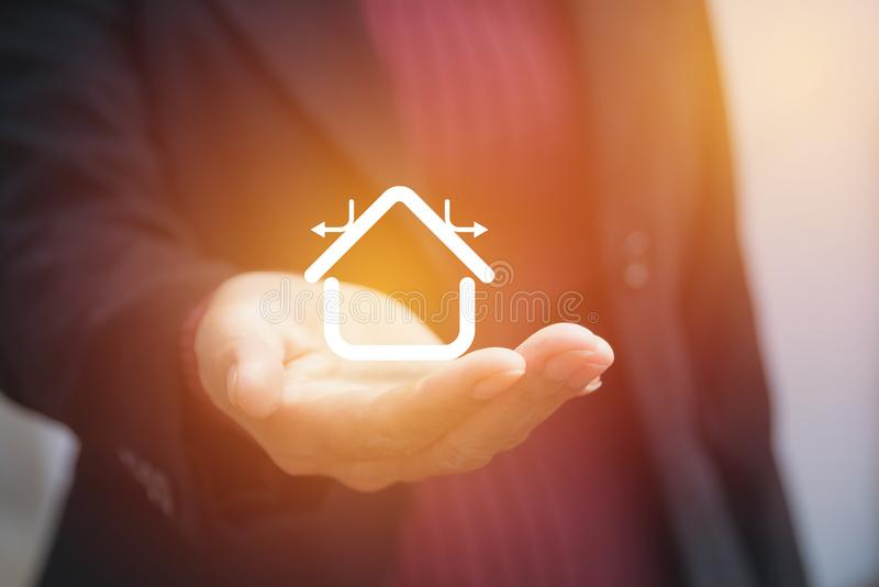Hand of businesswoman holding house icon stock image