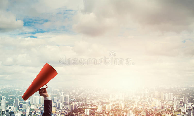 Hand of businesswoman holding red paper trumpet against cityscape background. Close of businesswoman making announcement in paper trumpet royalty free stock photos