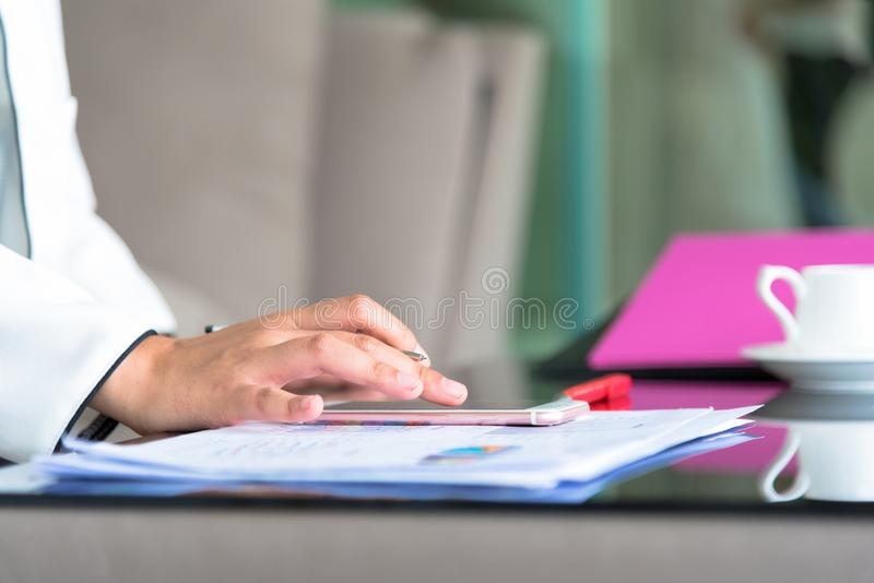 Hand of businesswoman holding with silver pen and playing a phone on documents in the office interrior stock images