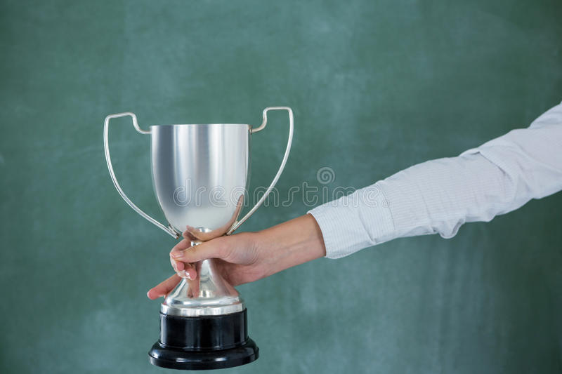 Hand of businesswoman holding trophy stock photography