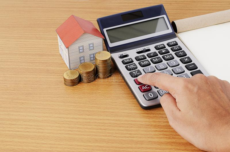 Hand on calculator with coins stack and paper house for mortgage. Loans concept royalty free stock photos