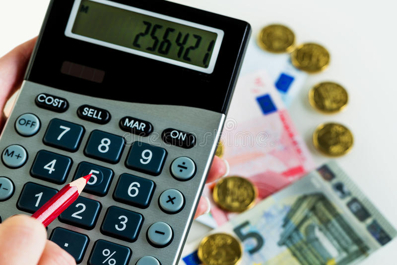 Hand with calculator and money stock image