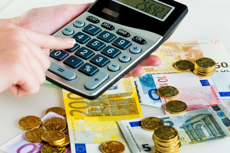 Hand with calculator and money stock images