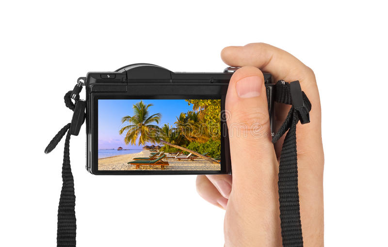 Hand with camera and Maldives beach photo (my photo). Isolated on white background royalty free stock photography