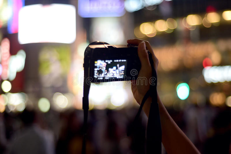 HAND CAMERA TAKING PHOTOS IN A BUSY CITY. A photo of a woman`s hand holding a camera and taking photos of the city lights at night in a busy city. Photo taken in royalty free stock photography