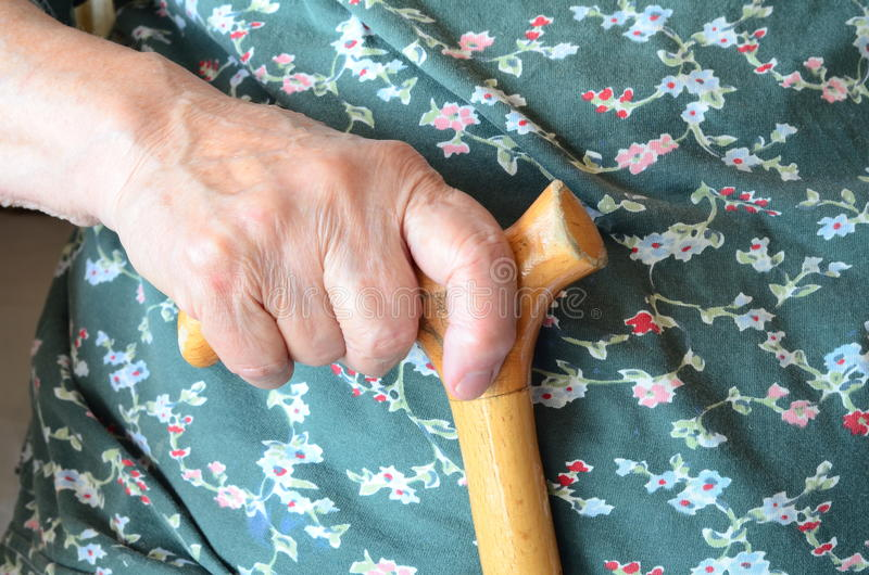 Hand on cane. A senior person holding a wooden cane royalty free stock photos