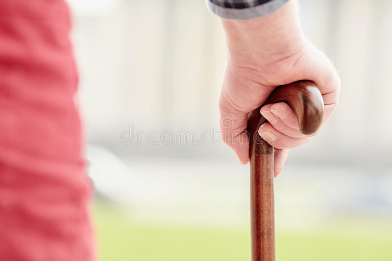 Hand with cane closeup. Close up of walking stick in senior male hand outdoors - recovery concept stock photos
