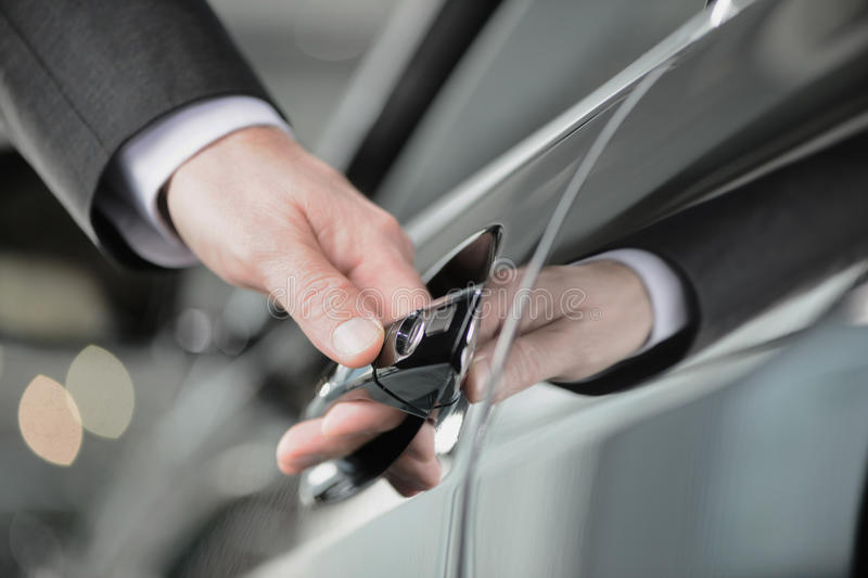Hand on the car handle. Businessman holding his hand on the casr handle stock images