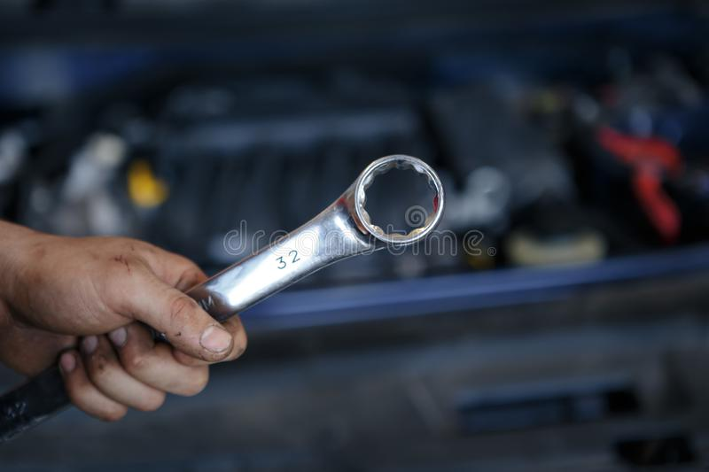 Hand of car mechanic with wrench. Auto repair garage. stock image