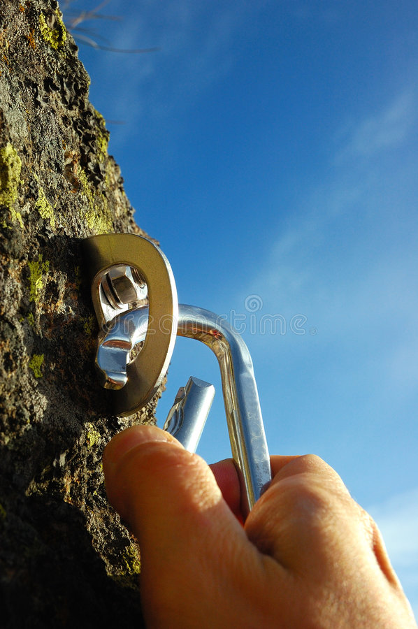 Hand carabiner. Hand attaching carabiner to a rock anchors stock photography