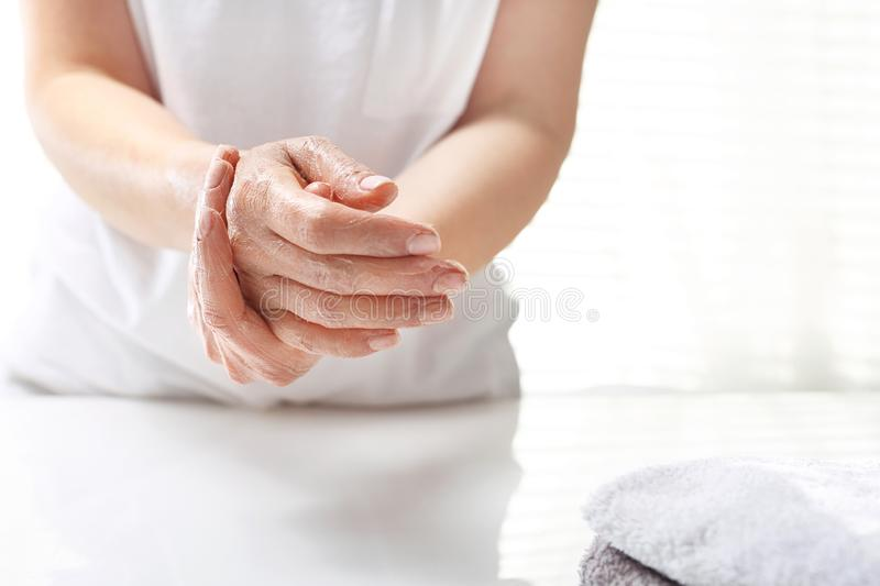 Hand spa. The woman peels the skin of the hand. Hand skin care stock photography
