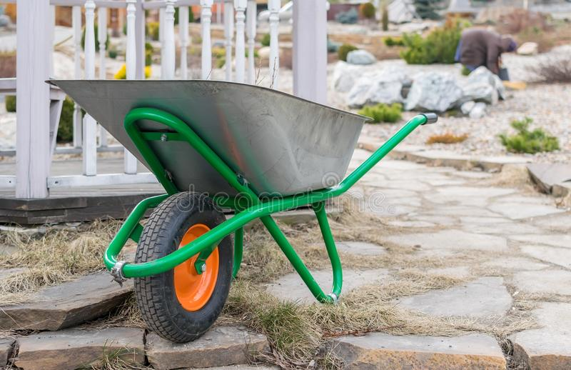 A hand cart with a wheel for garbage collection, construction and household stands on the background of the well groomed and ennob stock photos