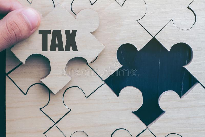 Hand carved wooden puzzle. Write the word `Tax` wait to fulfill home shape for build dream home. stock photos