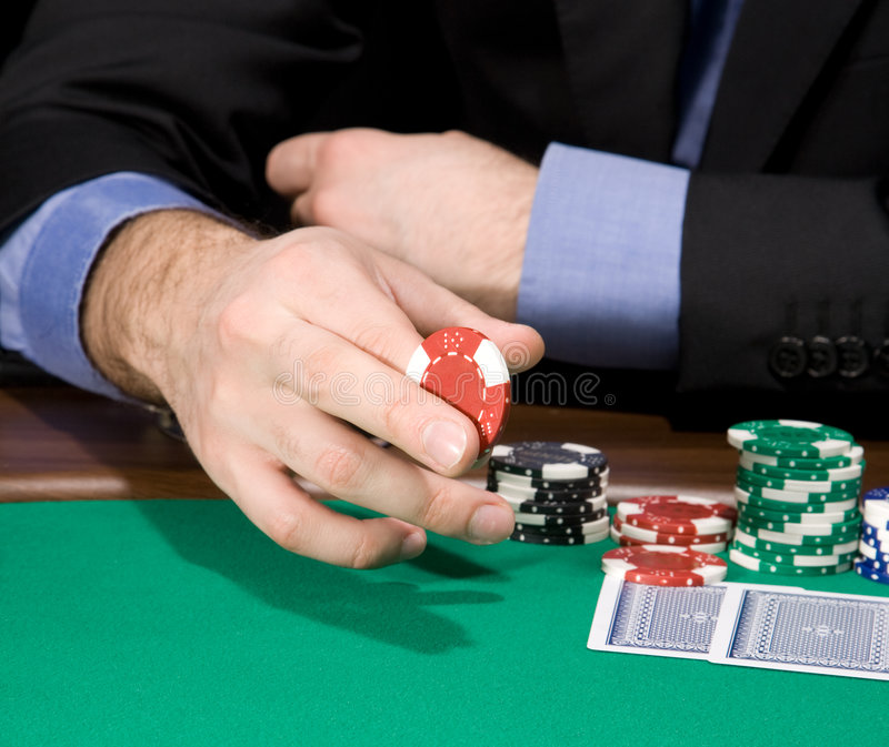 Hand with casino chip. Hand of man holding casino chip over green felt stock images
