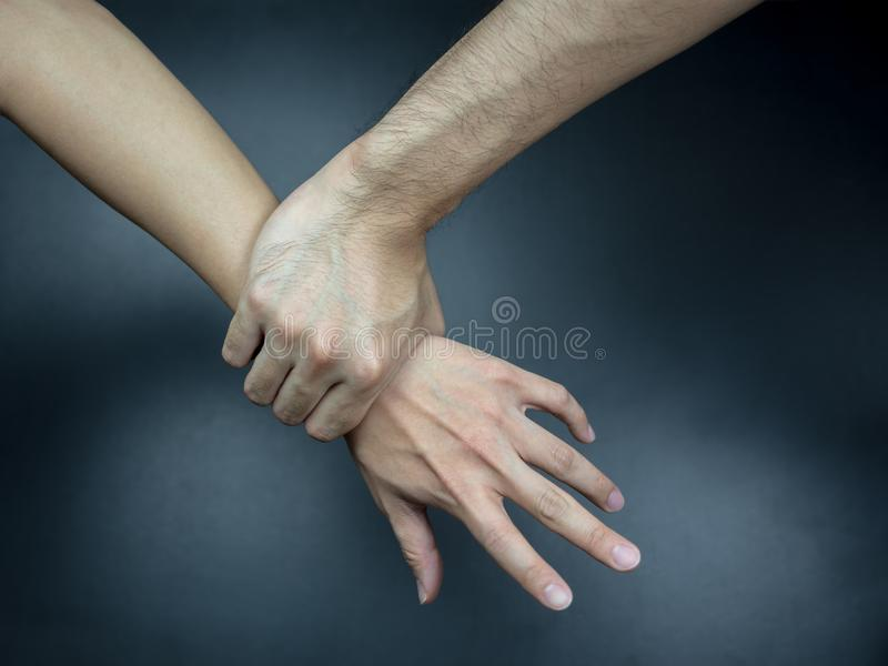 Hand catching others wrist, getting caught stock photo
