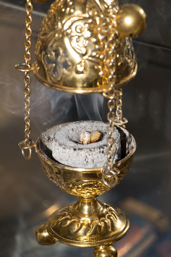 Hand censer with burning incense on hot charcoal inside. During celebration in orthodox Church. Fragrance smoke rising up. Close-up. Vertical photography royalty free stock photo