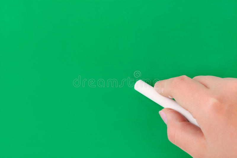 Hand with chalk writing on blackboard royalty free stock images