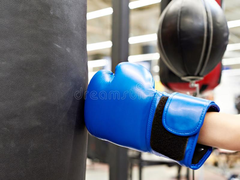 Hand of child in boxing glove and punching bag. Hand of a child in a boxing glove and punching bag stock images