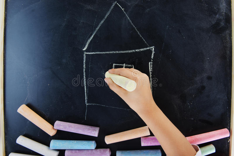 Hand of child writing. On blackboard royalty free stock photos