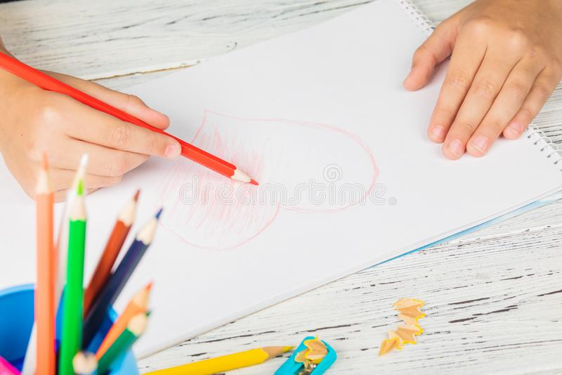 Hand of children drawing red heart with colored pencil on white. Paper on wooden table stock photography
