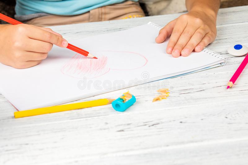 Hand of children drawing red heart with colored pencil on white paper on wooden table.  royalty free stock image