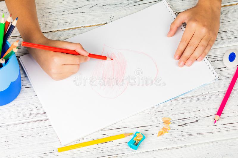 Hand of children drawing red heart with colored pencil on white paper on wooden table royalty free stock images