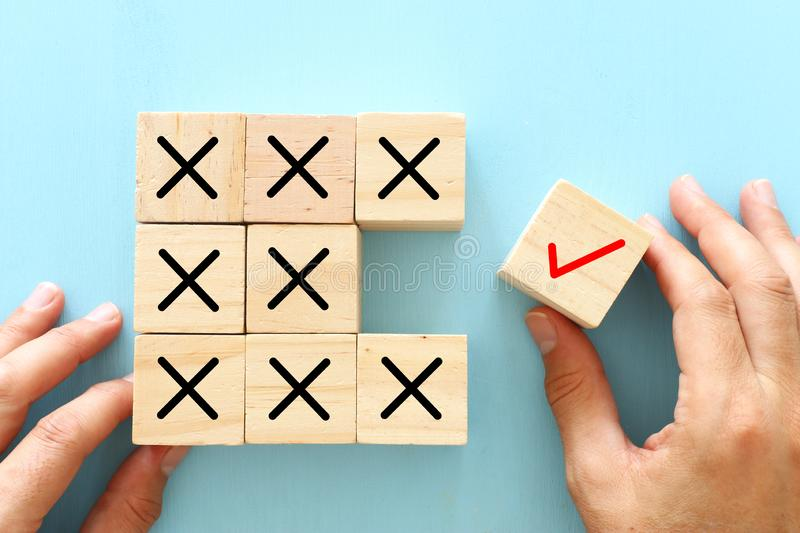 A hand chooses a cube with check mark symbol instead of cubes with cross sign. An idea of positive thinking and change of mind stock images