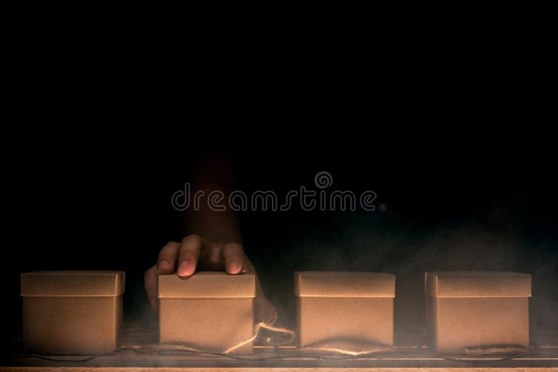 Hand choosing a box. On wooden table in mysterious concept stock photo