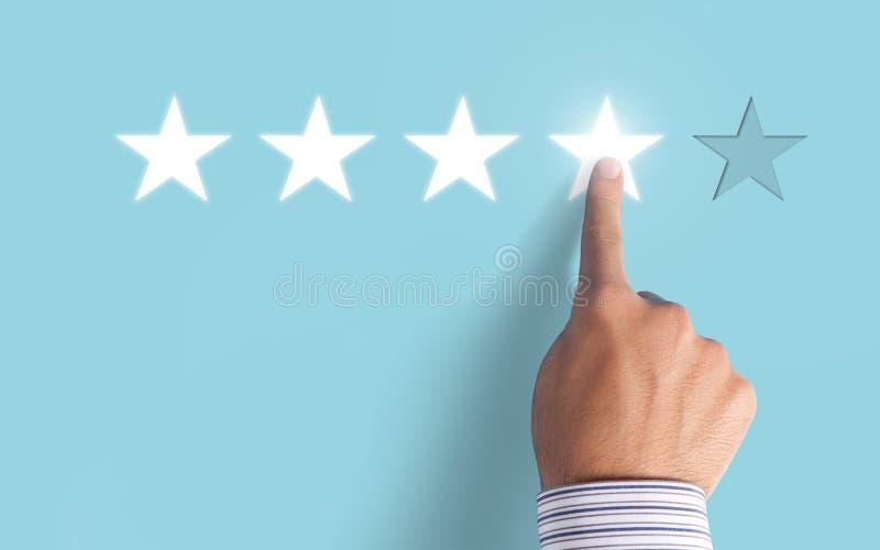 Hand choosing 4 stars on blue background - Good feedback concept. Hand choosing 4 stars on blue background - Good feedback stock photos