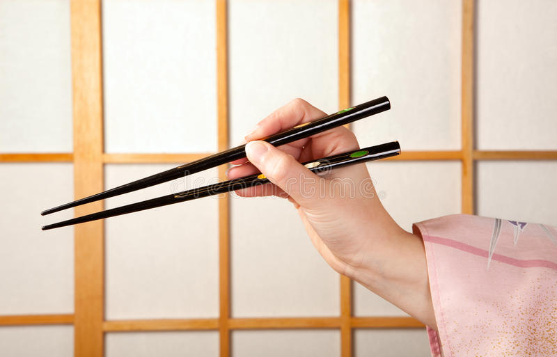 Hand with chopsticks stock photography