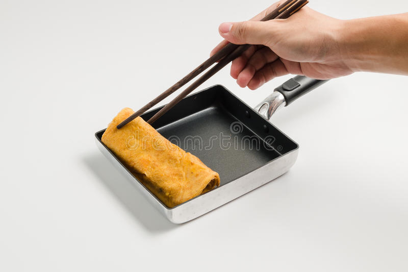 Hand with chopsticks grip roll fried egg stock image