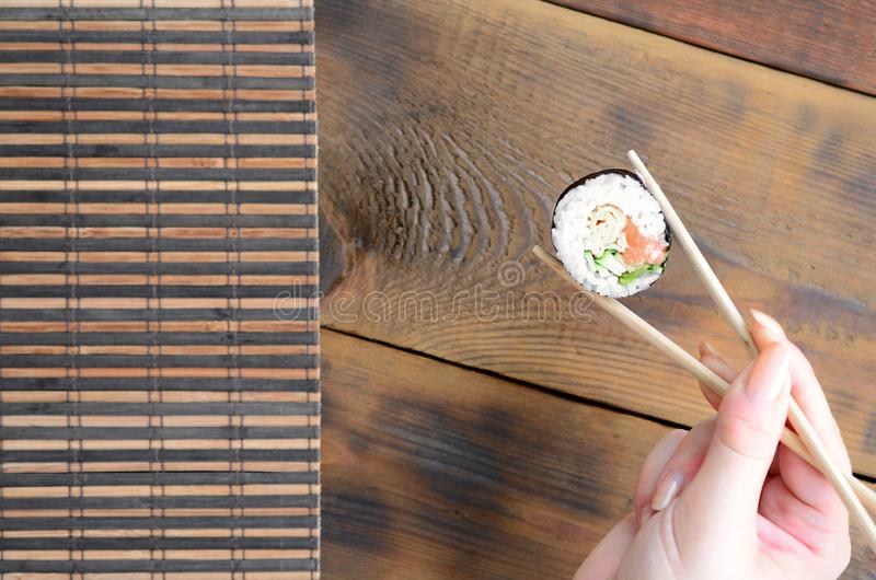 A hand with chopsticks holds a sushi roll on a bamboo straw serwing mat background. Traditional Asian food stock images