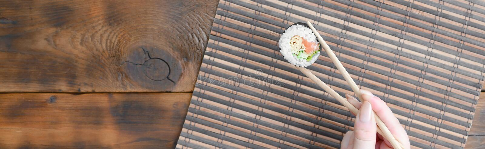 A hand with chopsticks holds a sushi roll on a bamboo straw serwing mat background. Traditional Asian food royalty free stock image